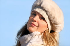 Blond girl in a fur hat Stock Images