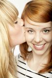 Blond girl give red haired girl kiss Royalty Free Stock Photos