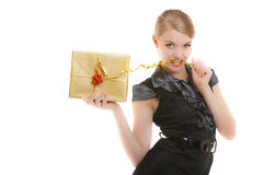 Blond girl with golden christmas gift box ribbon in teeth. Holiday. Royalty Free Stock Photography
