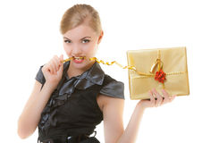 Blond girl with golden christmas gift box ribbon in teeth. Holiday. Royalty Free Stock Photos