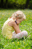 Blond girl on grass. Beautiful blond girl sitting on meadow Stock Image