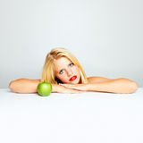 Blond girl and green apple Royalty Free Stock Image