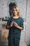 Blond girl in green dress poses near christmas tree Royalty Free Stock Images
