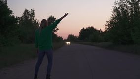 Blond girl stand at the road. Blond girl in green pullover stand at the road. Lady corrects her hair and start to dance slowly. Spending time outdoor stock footage