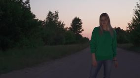 Blond girl stand at the road. Blond girl in green pullover stand at the road. Lady corrects her hair and start to dance slowly. Spending time outdoor stock video