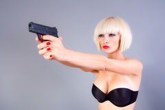 Blond girl with the gun. Portrait of attractive blond girl holding a gun stock photo