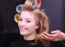 Blond girl hair curlers rollers by hairdresser in hairdressing salon Royalty Free Stock Image