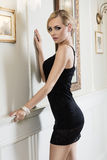 Blond girl with hair style in luxury ambient. Stunning blond woman in short sexy black dress near a wall in a very luxury indoor , she is looking in camera Stock Image