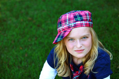 Blond girl in hat in grass Royalty Free Stock Image