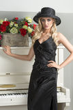 Blond girl with hat near piano Stock Photo