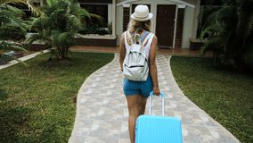 The blond girl in a hat and overalls settles in a tropical hotel with a blue bag.