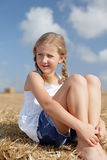 Blond girl on a haystack Royalty Free Stock Photography