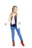 Blond girl with a headphones. Listening to music and dancing. Royalty Free Stock Images