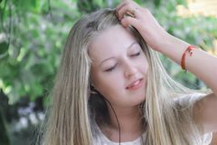 Blond girl with headphones, portrait. Blond girl with headphones portrait royalty free stock images