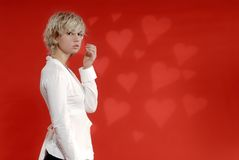 Blond Girl, Heart Background. Beautiful young blond woman in profile, looking with serious expression toward camera.  Against a red heart-filled background Stock Photos