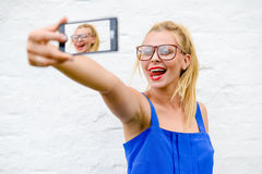 Blond girl in hipster glasses making selfie with Stock Images