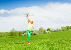 Blond girl holding airplane toy during running Royalty Free Stock Photography
