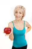 Blond girl holding apple and smiling. Royalty Free Stock Photo