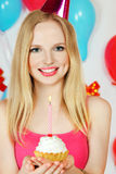 Blond girl holding cake with candle Stock Photo