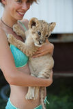 Blond girl holding cute little lion cub Royalty Free Stock Photography