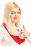 Blond girl holding a glass of water Stock Image