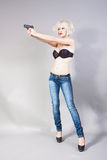 Blond girl holding a gun. Portrait of blond girl holding a gun Stock Image