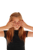 Blond girl holding her hands over eye's. A lovely young girl standing with her hands over her eye's isolated for white background stock photos