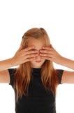 Blond girl holding her hands over eye's. Stock Photos