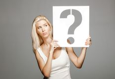 Blond girl holding a question mark sign. Beautiful blond girl in white dress holding a question mark sign Stock Image