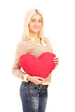 Blond girl holding a red heart-shaped pillow Stock Images
