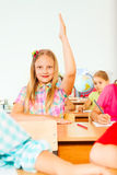 Blond girl holds hand up in class and smiles Stock Images