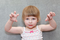 Blond girl holds her hands up like claws. Royalty Free Stock Photo