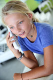 Blond girl at home talking on the phone Royalty Free Stock Images