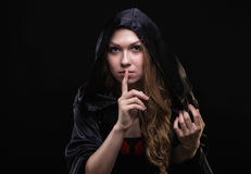 Blond girl in hood showing quiet gesture. On black background Stock Photo