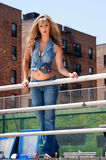 Blond girl in jeans. Sexy blond fashion girl dressed in jeans and jean top showing cleavage standing next to railing outdoors with buildings in the background Royalty Free Stock Photography
