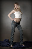 Blond girl in jeans posing in studio. Gorgeous young sexy blond girl posing in studio Stock Photography