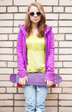 Blond girl in jeans, sunglasses holds skateboard. Blond teenage girl in jeans, sunglasses and colorful sporty clothes holds skateboard near by gray urban brick stock images