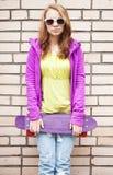Blond girl in jeans, sunglasses holds skateboard Stock Images