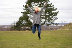 Blond girl jumping joyfully. Naturally blond girl with curly hair, jumping outside Royalty Free Stock Photography