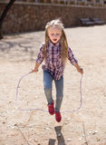 Blond girl jumping rope Royalty Free Stock Photos