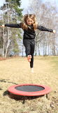 Blond girl jumping on trampoline. Barefoot blond girl - hairy kid in black clothes jumping on black and red kids´ small trampoline standing on grass of meadow Stock Photo