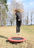 Blond girl jumping on trampoline. Blond girl - hairy kid in black clothes and white socks jumping and twisting on black and red kids´ small trampoline standing Royalty Free Stock Photos