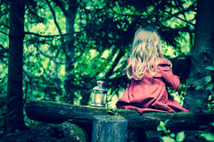 Blond girl with lantern sitting in forrest Royalty Free Stock Photos