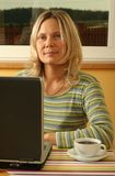 Blond girl with a laptop. Pretty blond caucasian woman working at home using her laptop Royalty Free Stock Photo