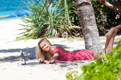 Blond girl with a laptop on tropical beach Stock Images