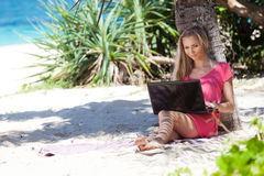 Blond girl with a laptop on tropical beach Stock Photos