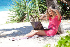 Blond girl with a laptop on tropical beach Stock Photo