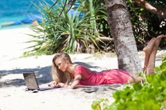 Blond girl with a laptop on tropical beach Royalty Free Stock Photography