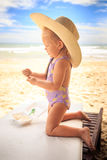 Blond Girl in Large Hat Stands on Knees with Spoon on Table Stock Photography