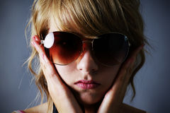 Blond girl with large sunglasses. Portrait of a pretty young blond teenager girl with large drak sunglasses, looking sombre, holding her face or covering her Stock Photography